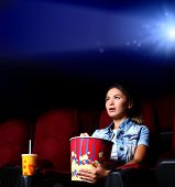 stock photo of watching movie  - One young girl watching movie in cinema - JPG