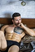 Shirtless Muscular Sexy Male Model Lying Alone On Bed In His Bedroom, Looking Away With A Seductive  poster