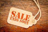 Sale ends soon sign - red stencil text on a cardboard price tag against rustic wood poster