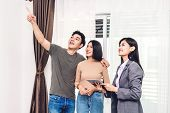Real Estate Agent Holding Tablet And Talk With Young Couple In A House For Sale. Business And Real E poster