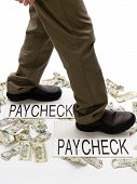 picture of paycheck  - Person stepping from paycheck to paycheck with spent money lying crumpled on the ground - JPG