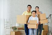 Joyful Asian Family Of Three Holding Moving Boxes In Hands And Looking At Camera With Toothy Smiles  poster