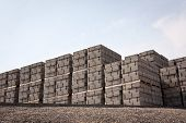 image of cinder block  - pallets of new concrete blocks under sunlight against blue sky - JPG