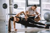 Male Personal Trainer Looking At Timer And Young Athletic Woman Doing Side Plank On Fitness Mat poster