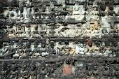 stock photo of asura  - Sculptured buddhas on wall of Terrace of the Elephant Cambodia