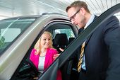 Woman buying new car in auto dealership and consulting salesman poster