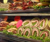 Many Appetizing Sandwiches And Sandwiches For Sale In The Window Of The Bar poster
