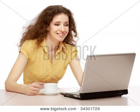 Beautiful smiling girl sitting at table with laptop and drinking coffee, isolated on white
