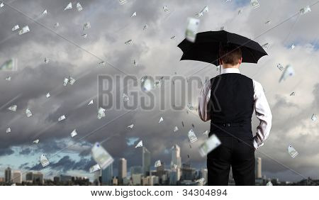 Business person under money rain
