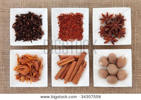 Saffron, star anise, cloves, cinnamon sticks, nutmeg and mace spice in white porcelain dishes over hessian background.