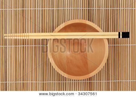 Japanese chopsticks and beech wood bowl over bamboo mat.