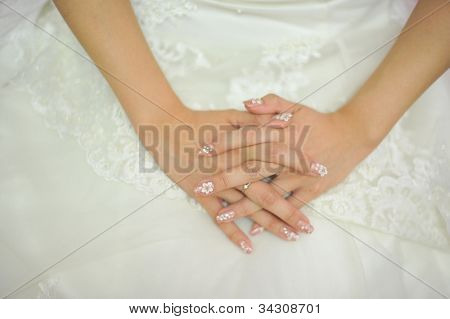 Bride hand on wedding dress