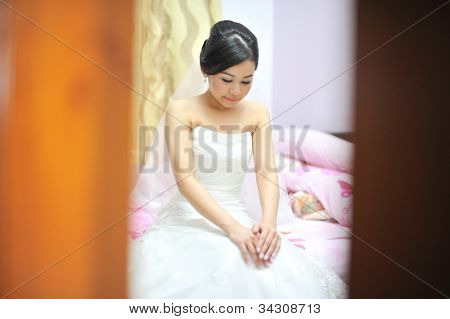 Bride sitting on her bed during wedding day