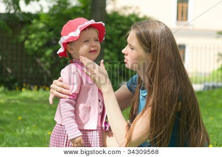 Little girl crying in mothers arm