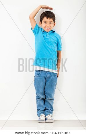 Boy growing tall and measuring himself on the wall