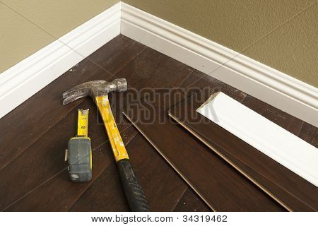Hammer, Laminate Flooring and New Baseboard Molding Abstract.