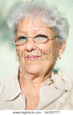 Old Woman With Eyeglasses Smiling And Looking At Camera