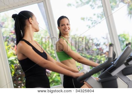 Pretty Young Girls Training On Fitness Bikes In Gym