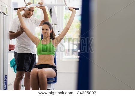 Personal Trainer Helping Woman Training In Wellness Club