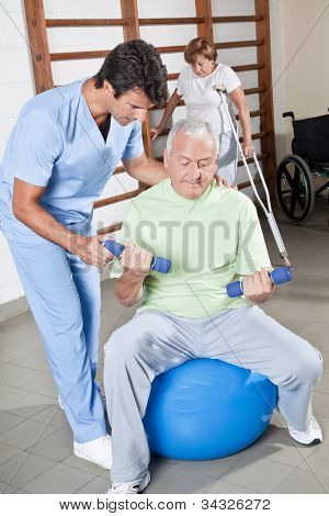 Male Physical therapist helping a patient.