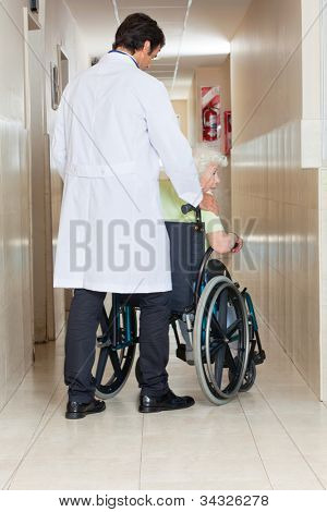 Rear view of a young doctor with senior woman sitting in wheel chair at hospital corridor