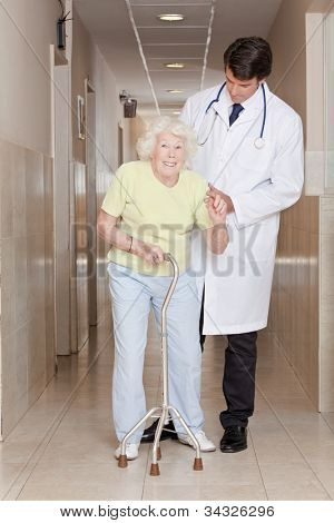 A doctor assisting a senior citizen onto her walking stick.