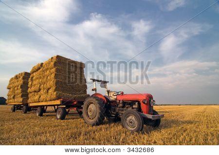 Equipo agrícola Tractor rojo con paja en remolque