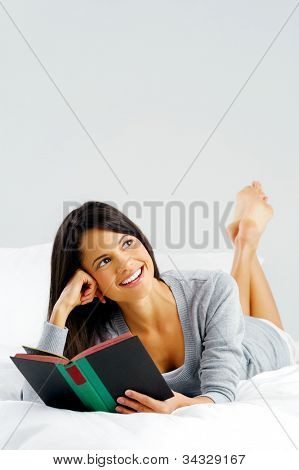 Woman reading a book in bed, lying on her stomach smiling happy and relaxed on a leisure day at home.