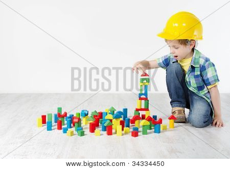 Boy In Hard Hat Playing With Blocks: Building City. Development And Construction Concept