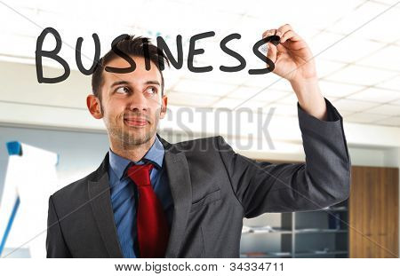 Businessman writing the word business on the screen