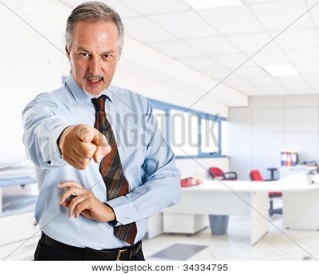 Mature businessman pointing his finger to you