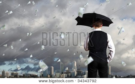 Image of a business person standing under money rain with umbrella