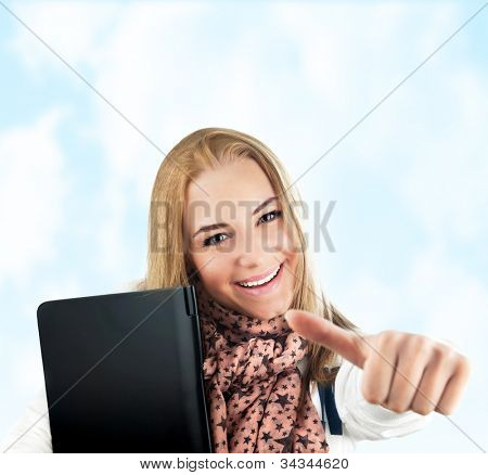 Happy cheerful student outdoor, pretty casual college pupil, closeup on cute young girl smiling, blond teen female model over blue sky, woman holding laptop, studying, thumbs up, success concept