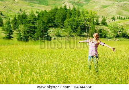 Happy girl enjoying nature, young woman on wheat field, beautiful female having fun with hands up, freedom concept, summer outdoor vacation, model teen over green natural background, sunny day joy