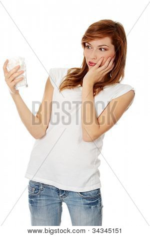 Young woman drinking cold drink, glass full of ice cubes and feels toothache, pain. Pretty red-haired girl in jeans and white t-shirt touching her cheek. Isolated on the white background.