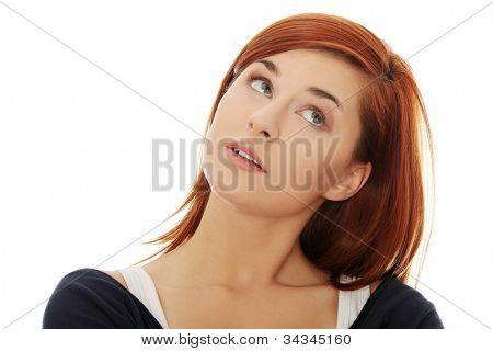 Face of young woman who is looking up, wondering and thinking. Pretty red-hair girl. Isolated on the white background.