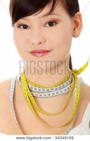 Young, pretty brunette with white-yellow tape-measure necklace. Pretty, slim woman with delicate smile in white t-shirt, could be on diet. Isolated on the white background.