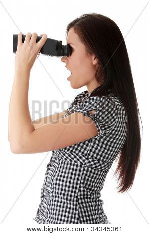 Surprised young woman standing and looking through the binoculars Pretty long-haired brunette watching somebody and laughing. Isolated on the white background.