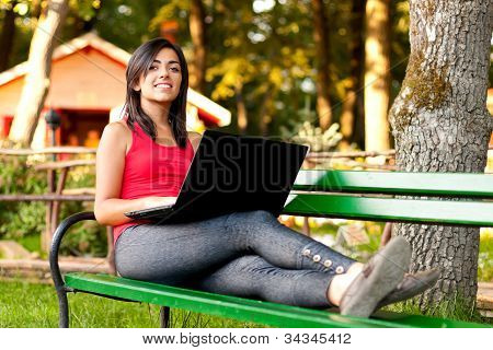 Girl With Laptop Laying On Bench