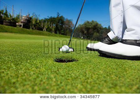 Golfista en el putting green, preparándose para poner