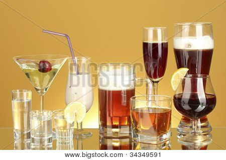 a variety of alcoholic drinks on yellow background