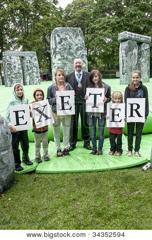 The Right Worshipful the Lord Mayor of Exeter Rob Newby stands with children who hold up letters tha