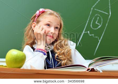 Portrait of a cute dreaming schoolgirl in a classroom.