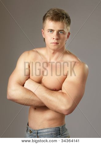 Strong man with a helathy body isolated over grey