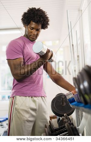 Young Black Man Taking Weights From Rack In Gym