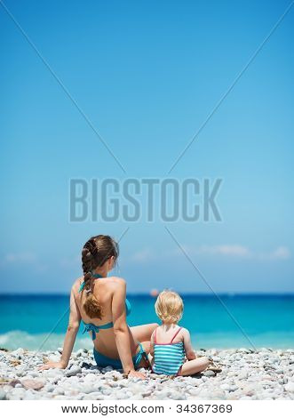 Mother Sitting With Baby On Beach Looking Into Distance. Rear Vi