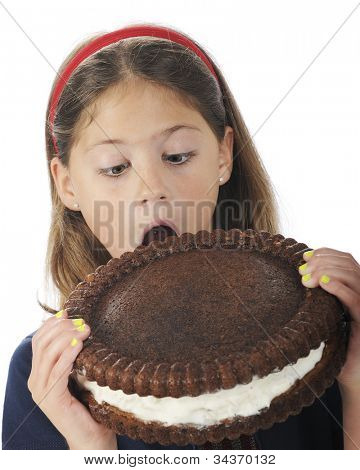 Closeup of an attractive elementary girl, mouth opened wide, preparing to bite into a giant, cream-filled cookie.  On a white background.