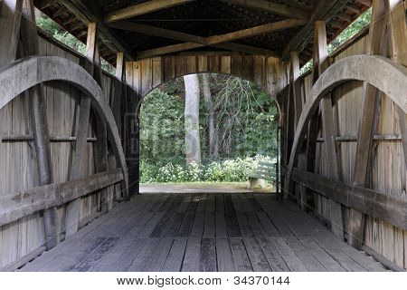 A view through an old covered bridge on a summer day.