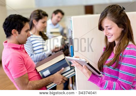 Woman with tablet computer reading an e-book and friends carrying heavy books