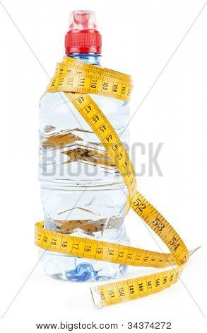 Water in bottle and a yellow tape measure on white